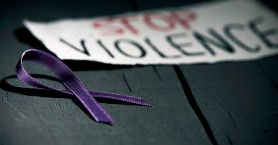 Un lazo morado y un letrero que dice Stop Violence