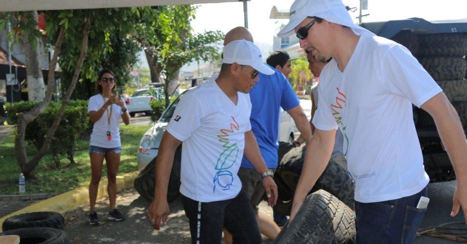 dos hombres participan en la recolección de llantas