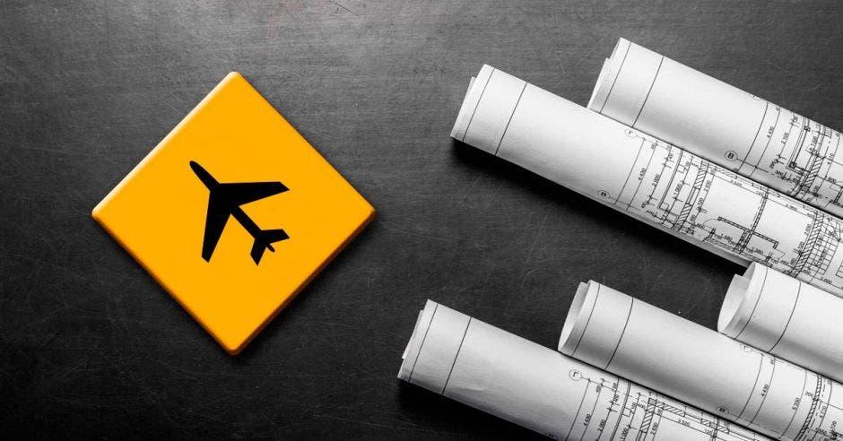 planos junto a un cuadrito amarillo con un dibujo de un avión