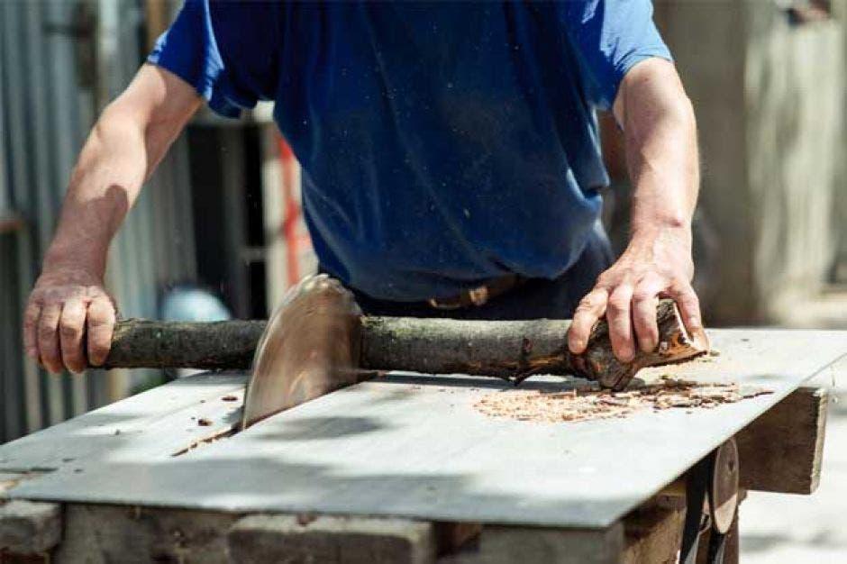 Un hombre cortando madera