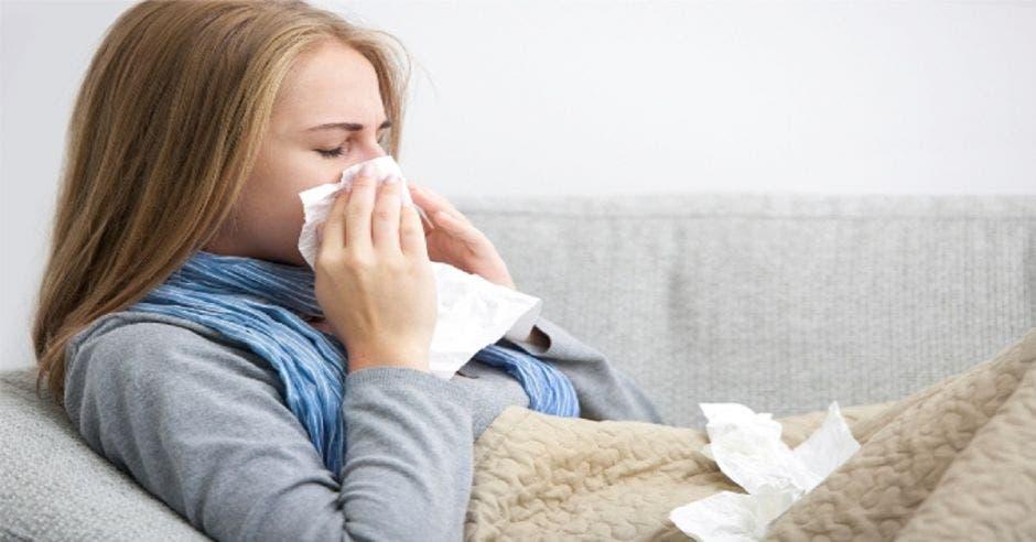 Una mujer con gripe acostada en un sillón