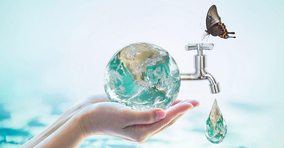 Una mano con un mundo y un grifo de agua saliendo una gota