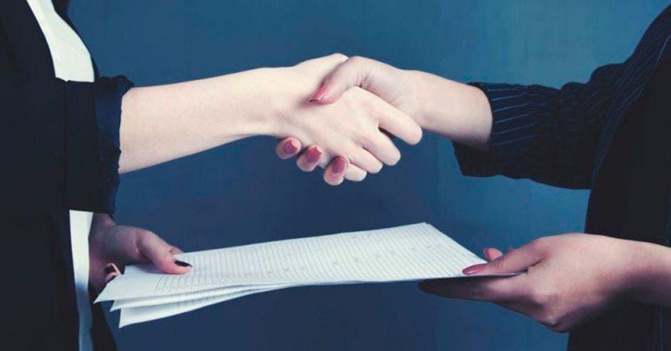 Dos personas dándose un apretón de manos y entregando un contrato