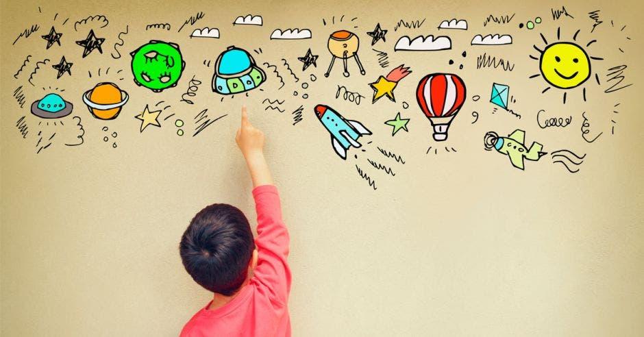 Niño con dibujos en la pared
