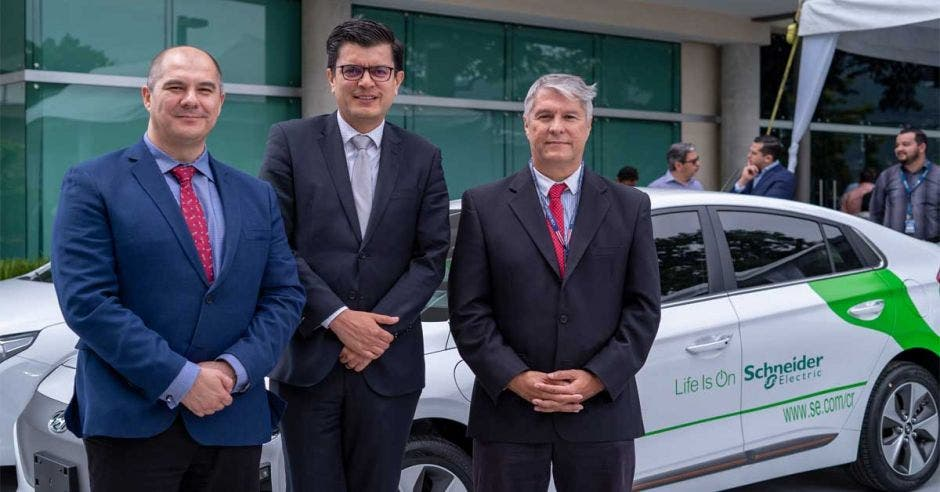 Carlos León de Garay, VP de Schneider Electric Centroamérica, Rolando Castro, Viceministro de Energía y Alan Blanco, Comisionado Presidencial de Movilidad Eléctrica junto a auto eléctrico