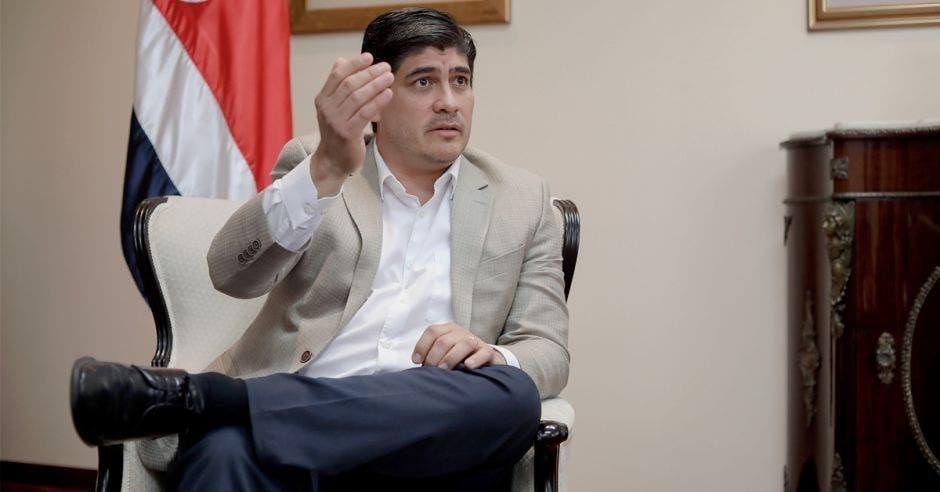 Carlos sentado en una silla dando una conferencia