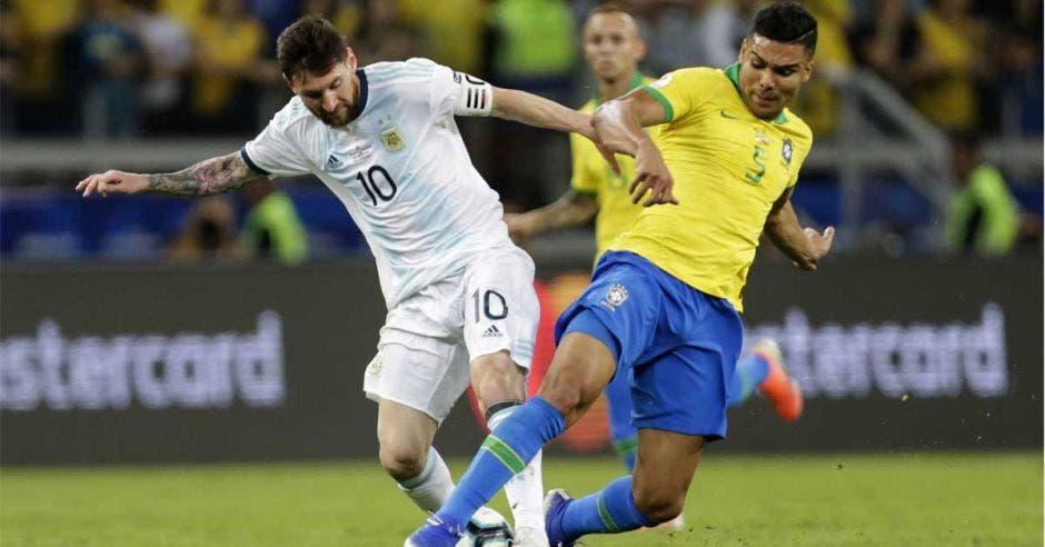 Lionel Messi y Casemiro disputan un balón