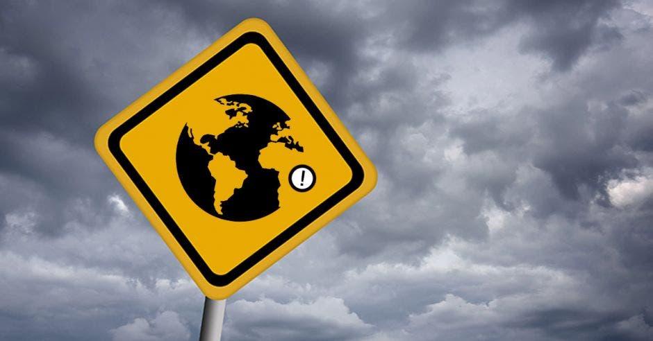 Un signo de advertencia con una imagen del planeta