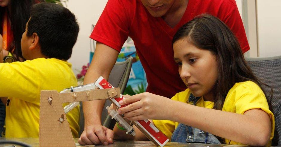 niña fabricando un brazo a partir de cartón
