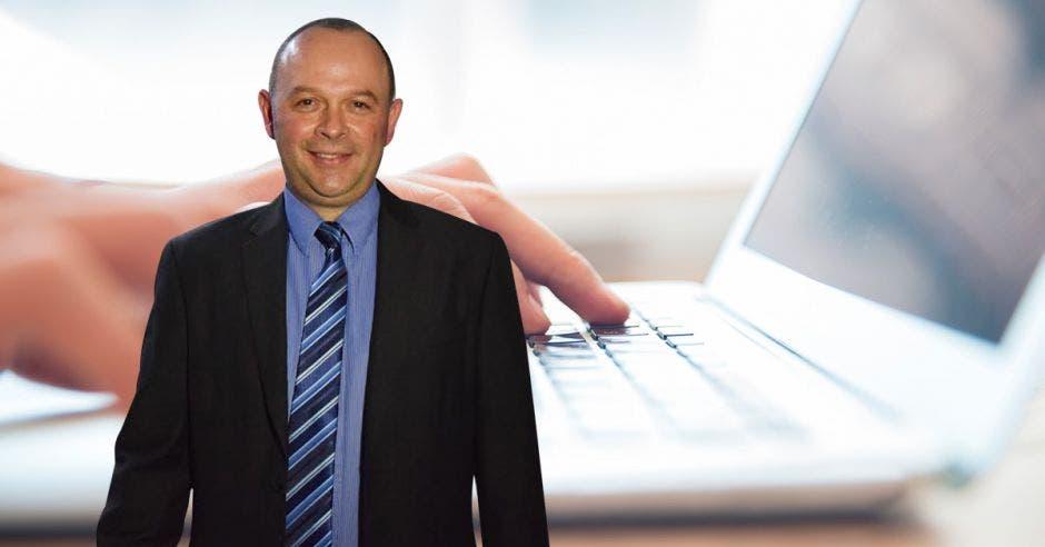 Allan Salas, gerente de ventas del BCR, con el fondo de una computadora.