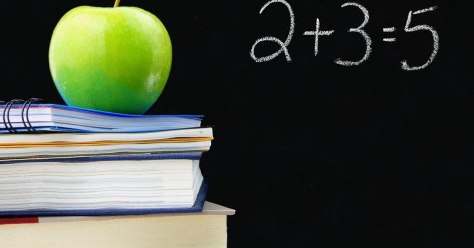 Una pizarra y unos libros con una manzana