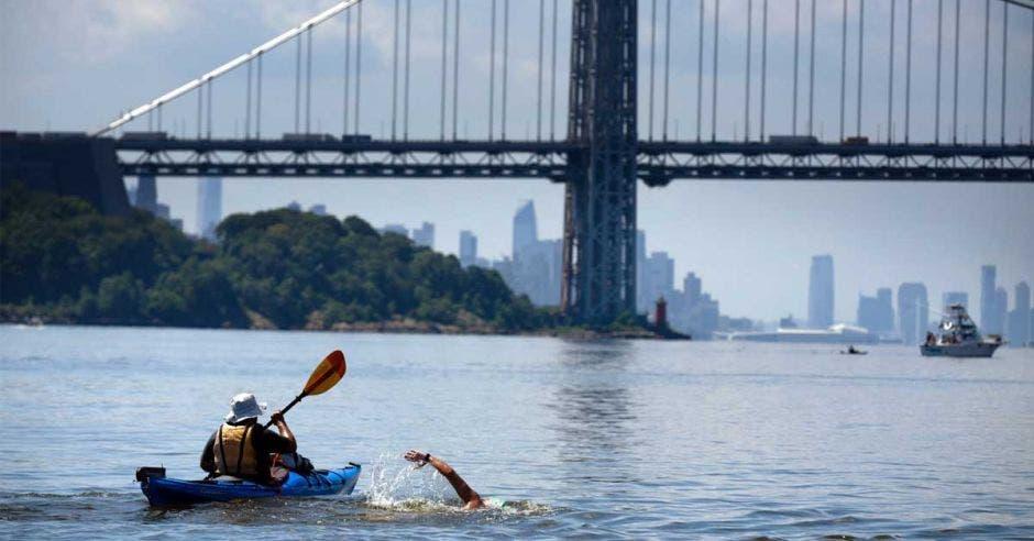 Persona nadando junto a kayak en manhattan