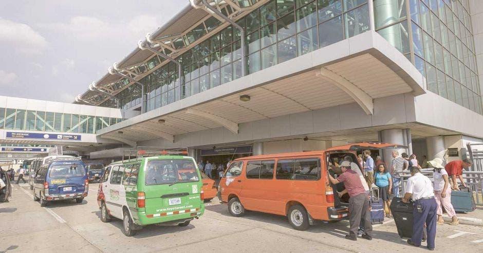 taxista del aeropuerto bajando maletas del carro