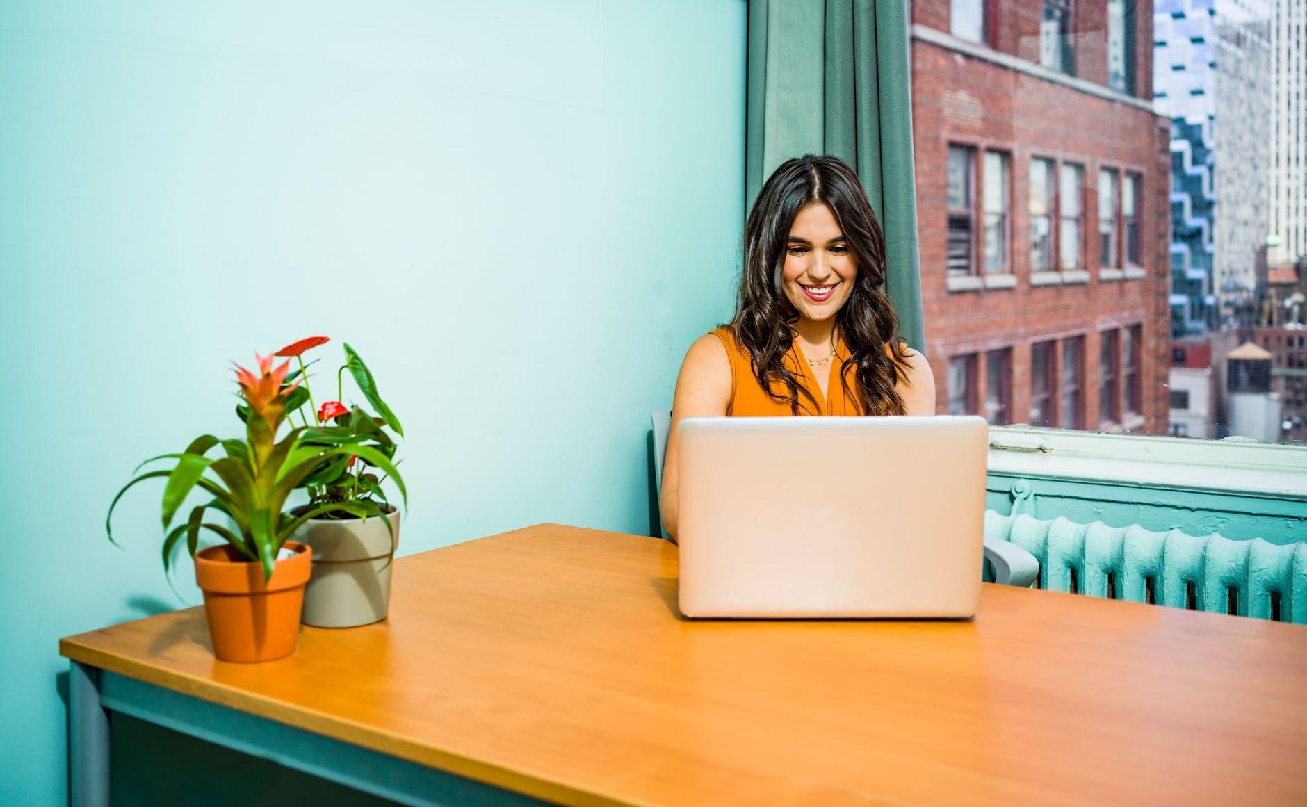 Mujer sonriendo frente a una laptop