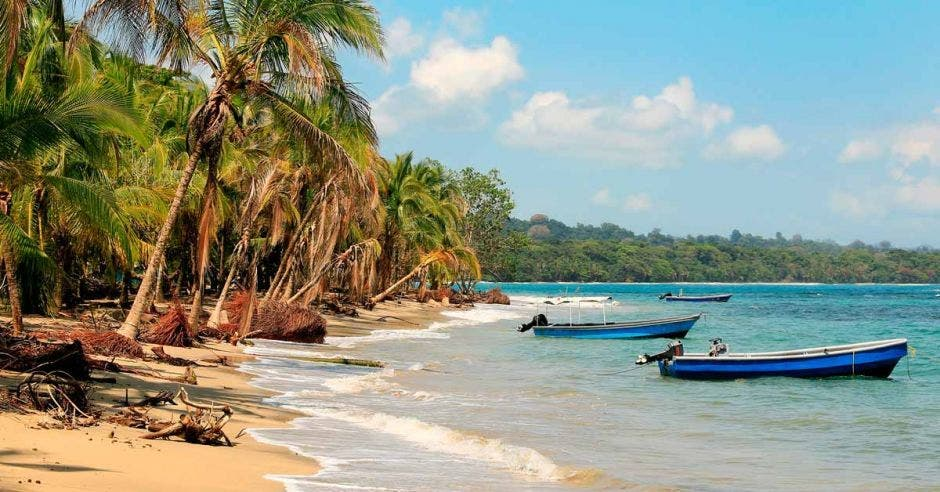 playa de arena dorada, mar turquesa, botes flotando