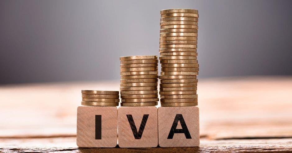 Bloques de madera deletrean IVA con monedas encima