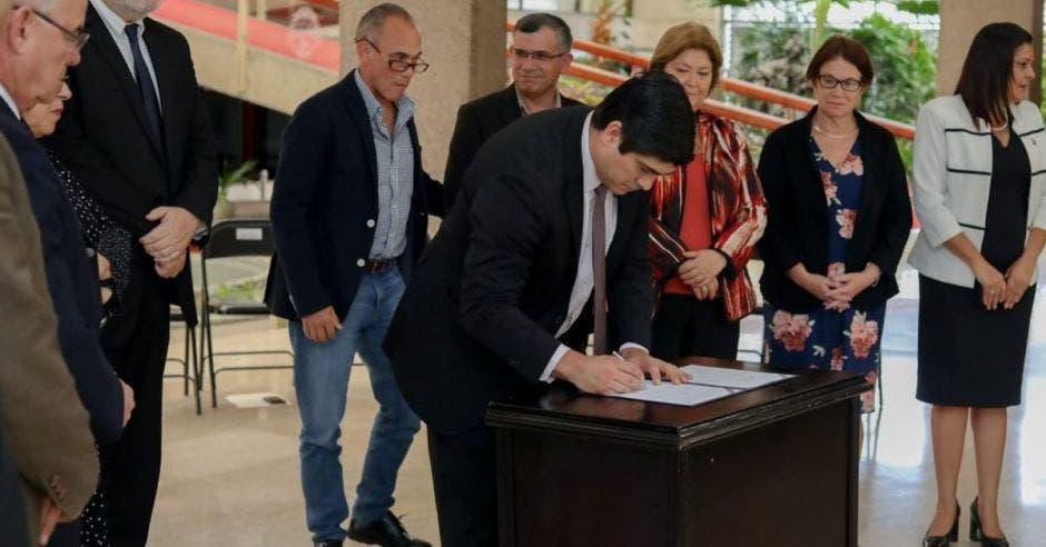 El Presidente, acompañado de varios ministros, durante la firma del decreto.