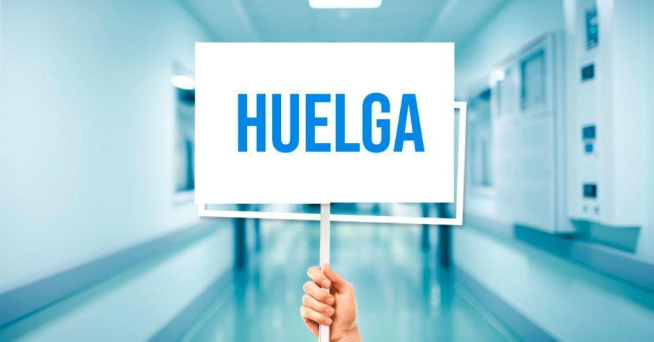 Un pasillo de un hospital y una mano con un cartel que dice huelga