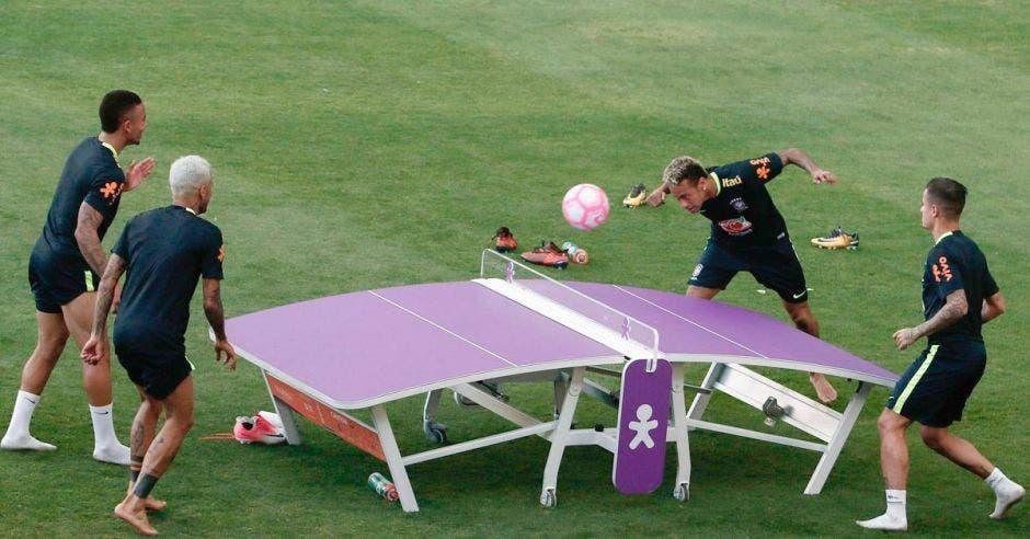 jugadores alrededor de una mesa jugando fútbol