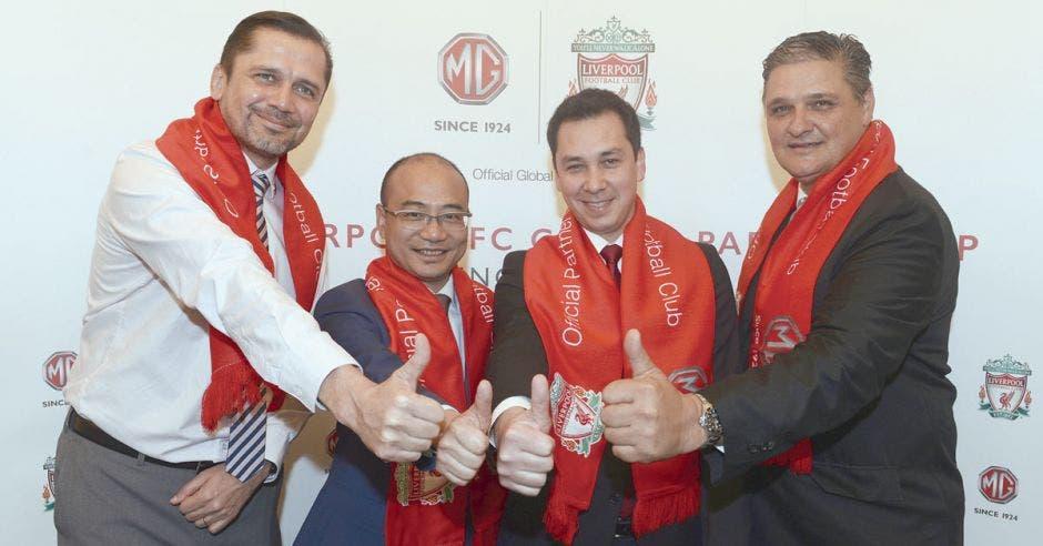 cuatro integrantes de mg saludando con el pulgar arriba