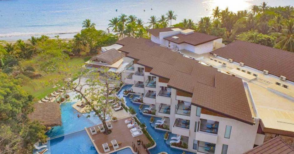 vista área del edificio de habitaciones, piscina y playa