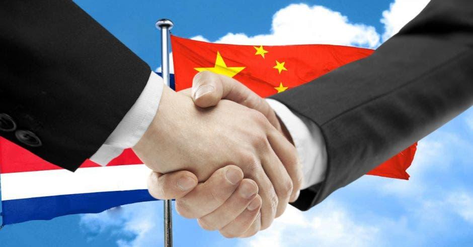 Apretón de manos con bandera tica y china