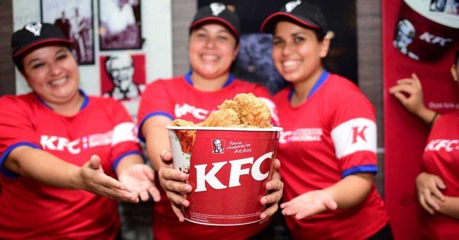trabajadores de KFC sosteniendo un tarro con pollo