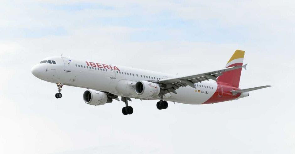 avión en el aire, blanco y la cola roja con amarillo