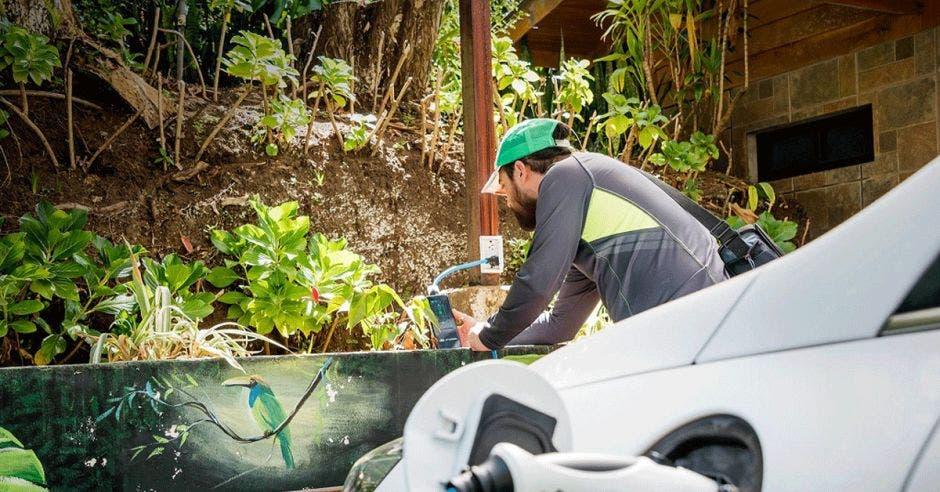 Un usuario carga su carro eléctrico en un local comercial de Monteverde