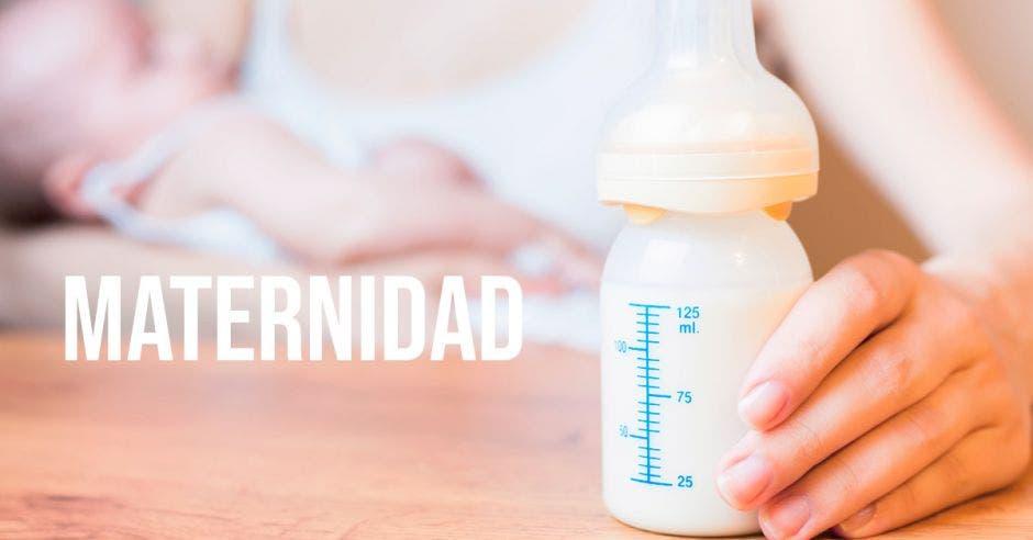 La palabra maternidad y una mujer con un niño en brazos y un chupón con leche