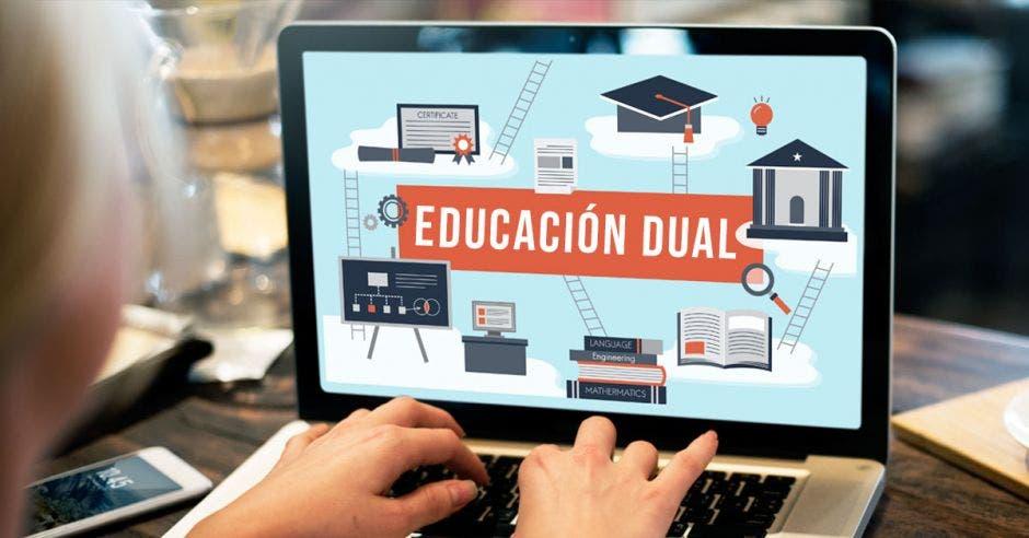 Una computadora con la palabra educación dual en el monitor y una persona con las manos en el teclado