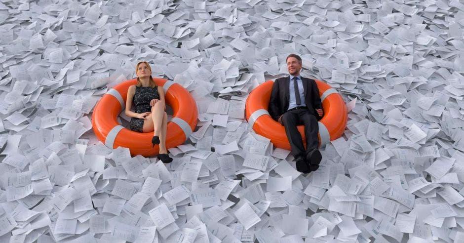 Dos empresarios nadando encima de un mar de papel