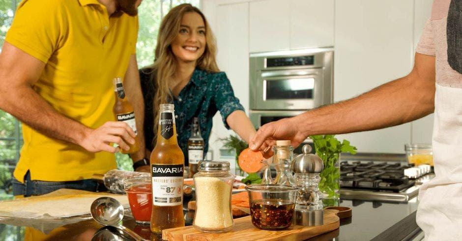 botella de Bavaria en una mesa, personas cocinando