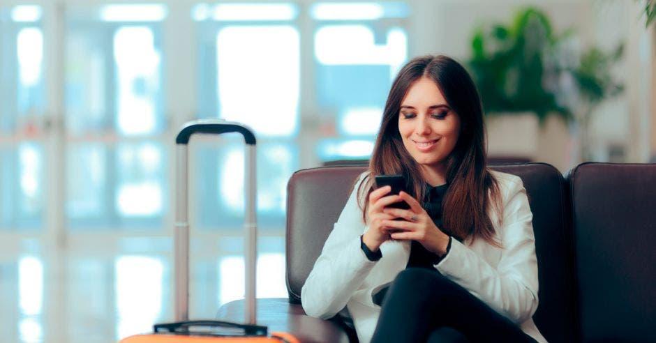 Mujer revisando celular antes de viajar