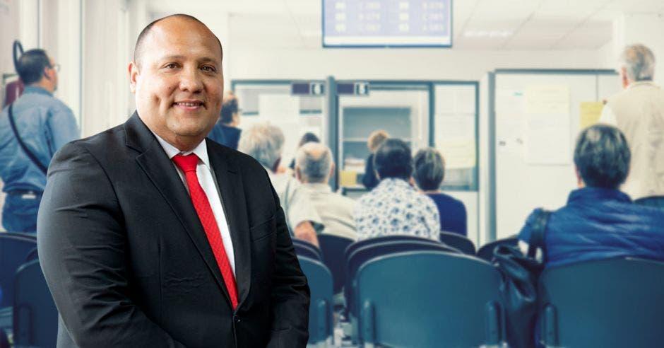 Mario Ruiz gerente médico de la CCSS y al fondo una imagen de personas esperando atención médica