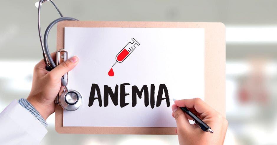 Un doctor con una pizarra en la que se lee Anemia