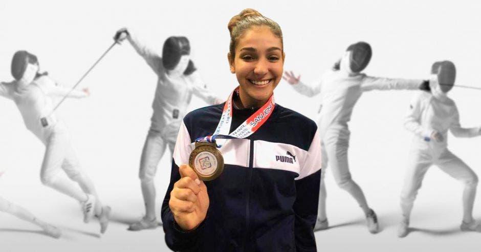 karina dymer con medalla y esgrimistas al fondo
