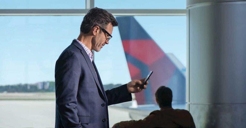 persona viendo el celular, está en el aeropuerto