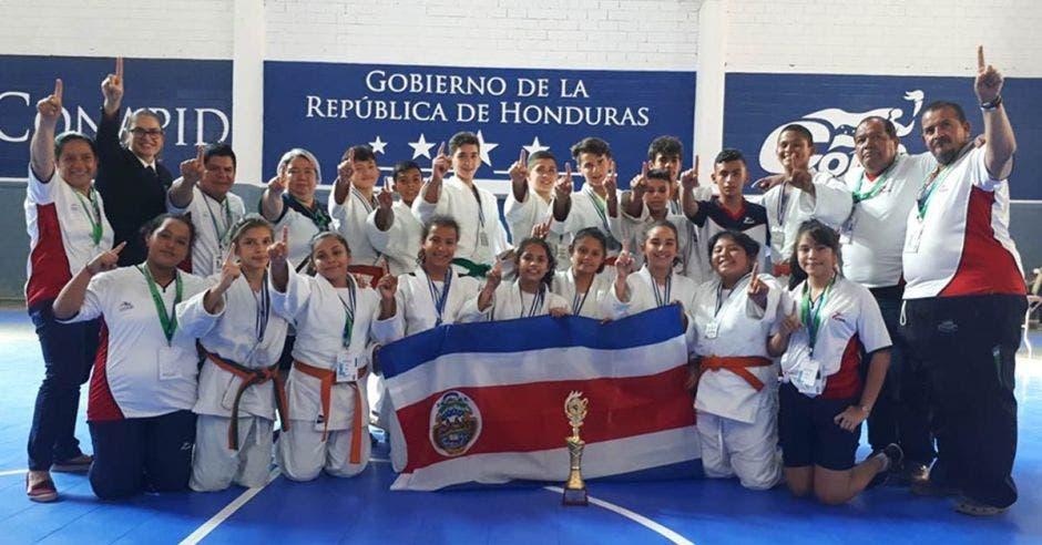 niños de jufo con bandera medallas y trofeo