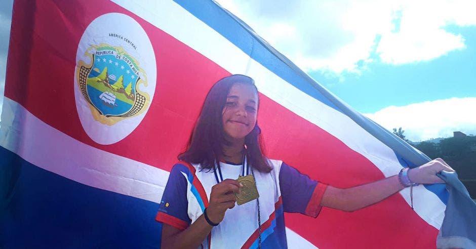joven con medalla y la bandera de costa rica