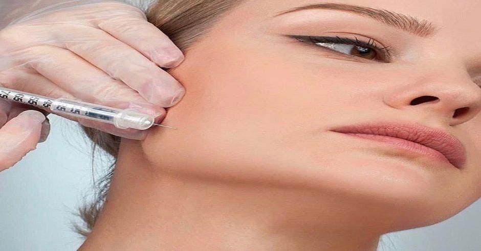 Una mujer aplicándose un procedimiento estético
