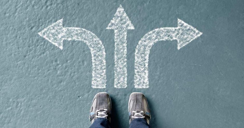 Unos pies en frente de tres flechas con direcciones distintas
