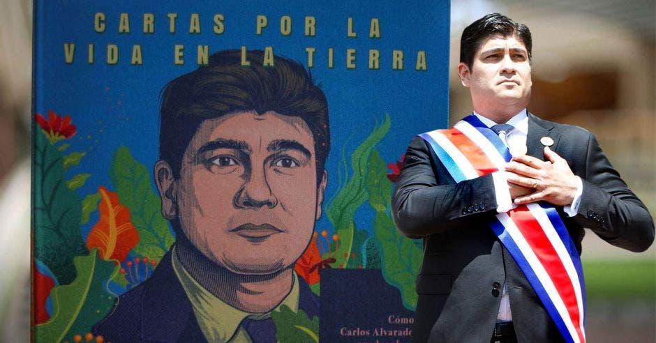 """Carlos Alvarado junto a un fondo del libro """"Cartas por la Vida en la Tierra"""""""