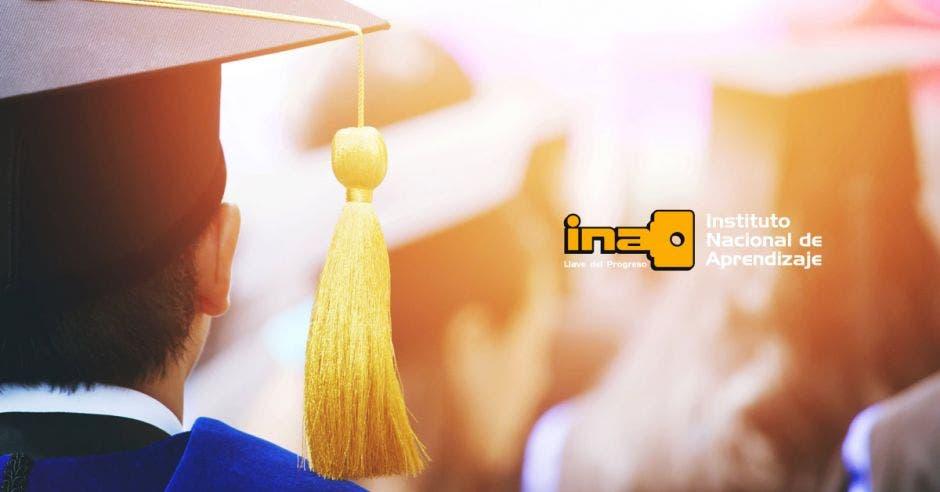 Un joven con un birrete de graduación y el logo del INA al lado