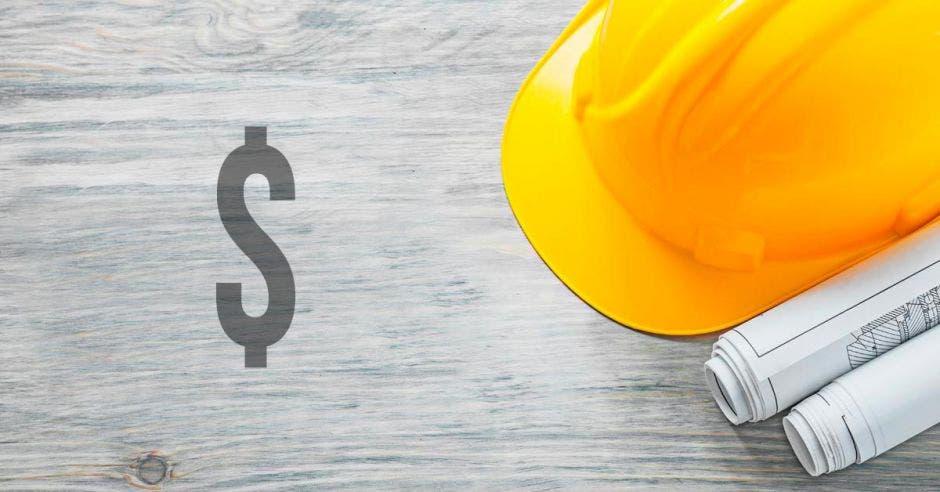 signo de dólar en una  mesa junto a planos y un casco de construcción