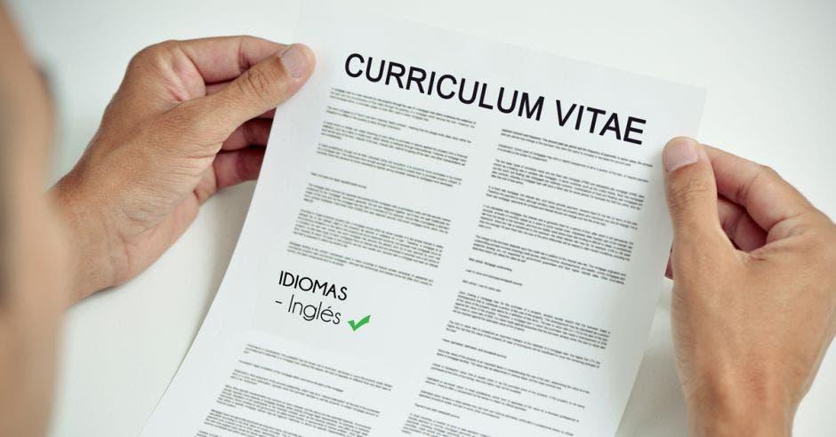 Unas manos sosteniendo un currículum vitae en donde destaca los idiomas