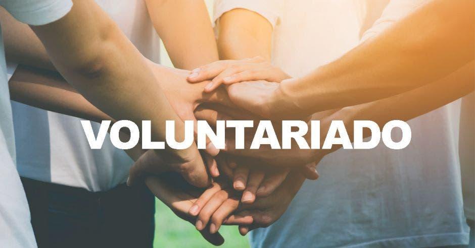 Varias personas uniendo las manos con la palabra voluntariado