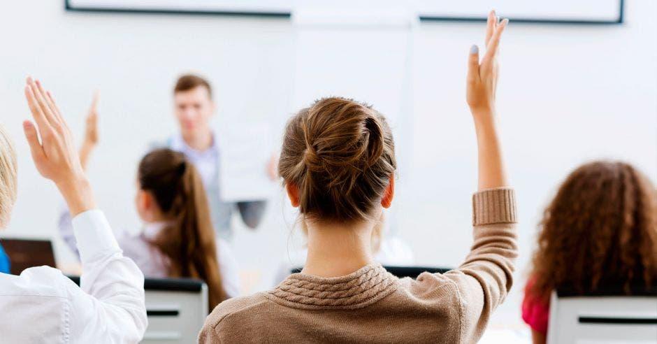 Jóvenes estudiantes levantando la mano en una clase