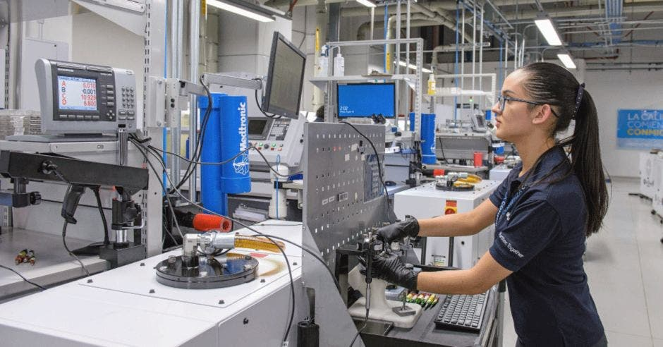 Una mujer opera una máquina de precisión