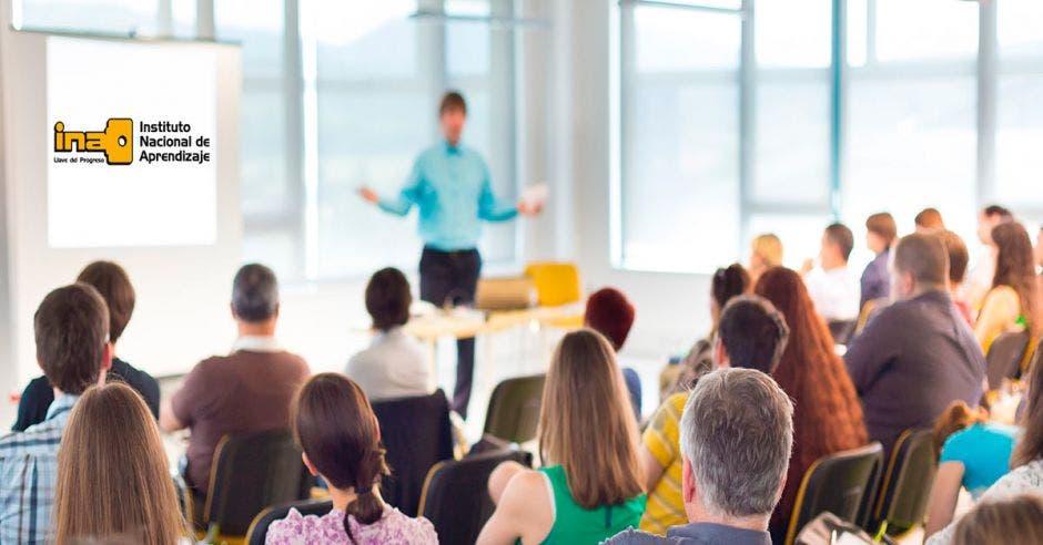 Una persona exponiendo ante una audiencia y un logo del INA